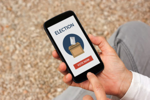 Hands holding smart phone with online voting concept on screen